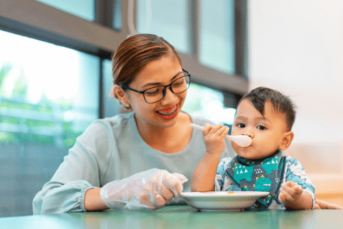 my first skool infant care meals teacher with a baby eating