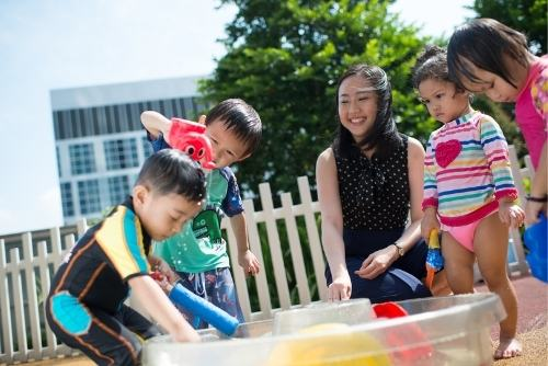 children engaging in water play outdoor learning in preschool singapore